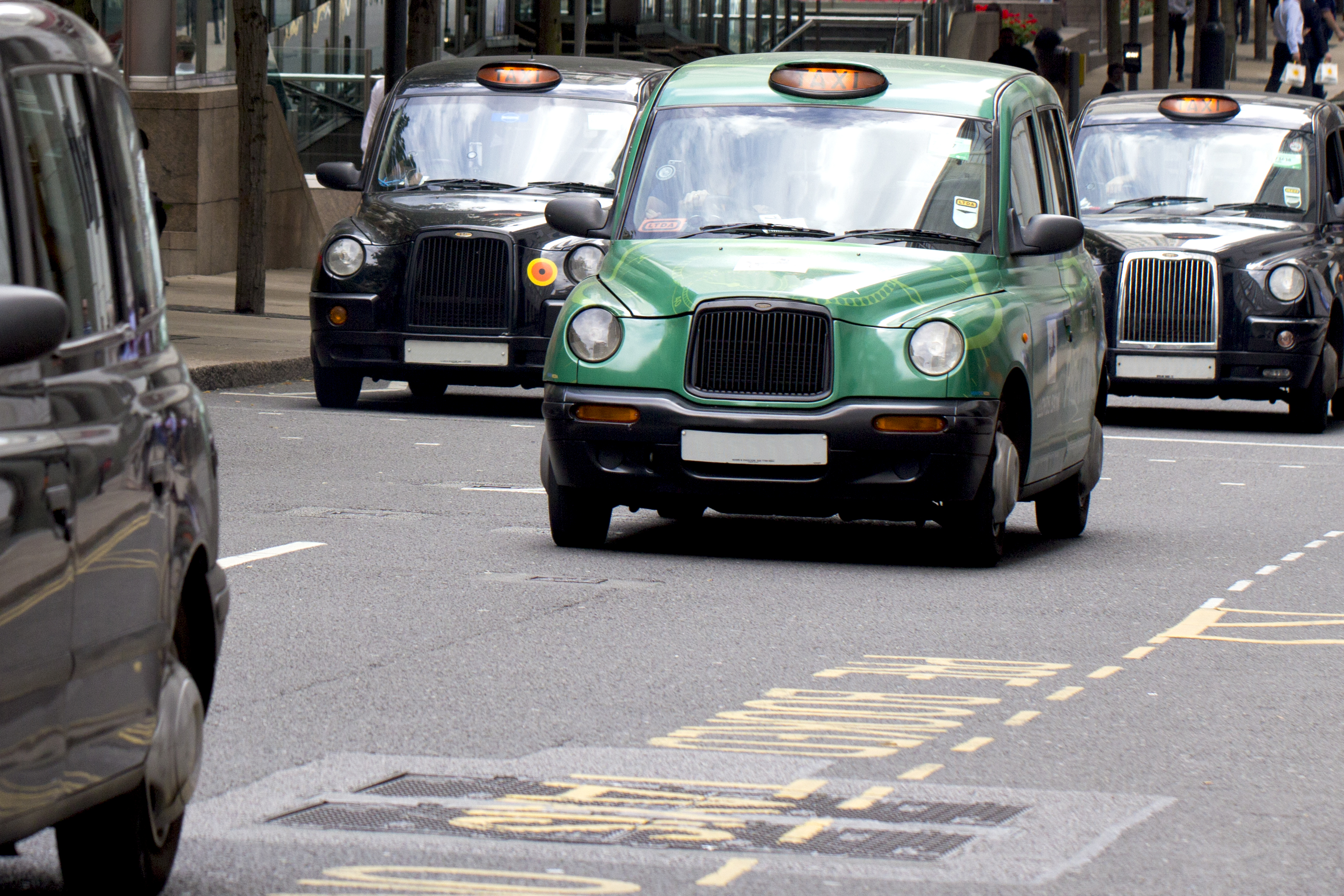 A Hackney Carriage travelling along a busy London road surrounded by other taxis