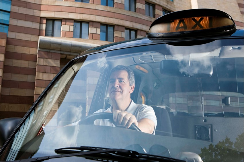 A taxi driver looking happy behind the steering wheel of his cab