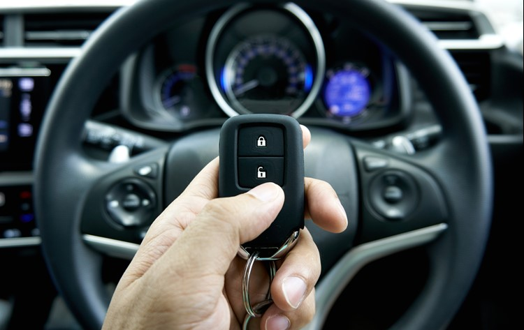 Driver holding key up in front of steering wheel of new car
