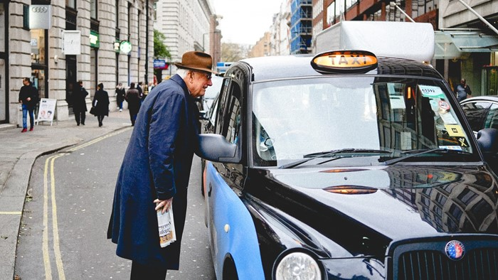 A taxi driver talking to a customer through the window