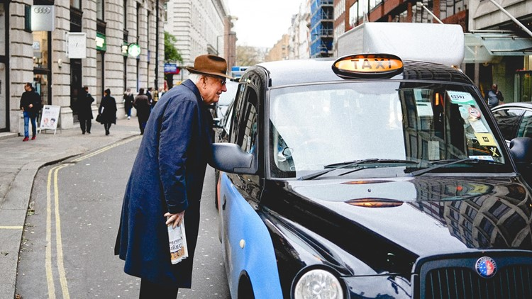 Elderly man catching a london taxi