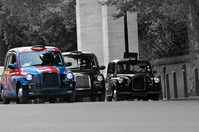 A hackney carriage wrapped in a Union Flag colour scheme driving through London
