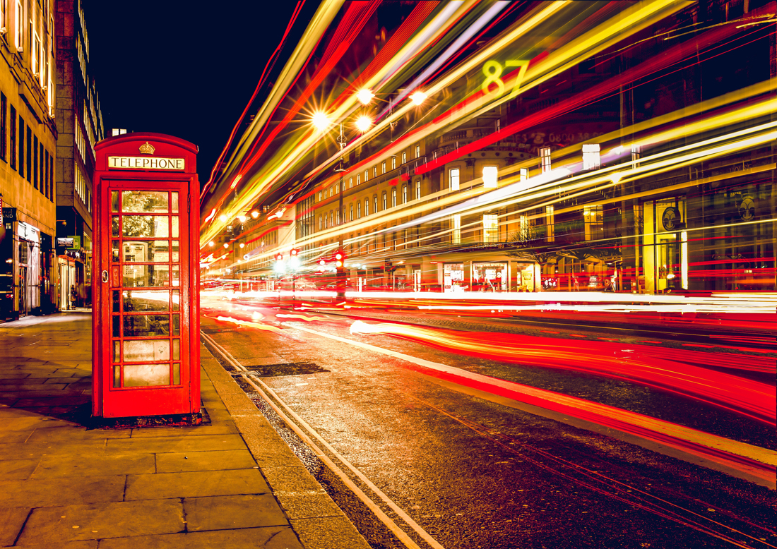 A red telephone box in London next to a street with a time lapse of lights going past