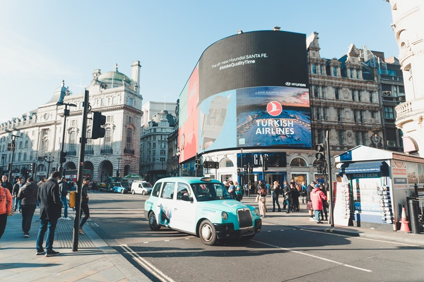 A blue Hackney Carriage driving through Piccadilly Circus