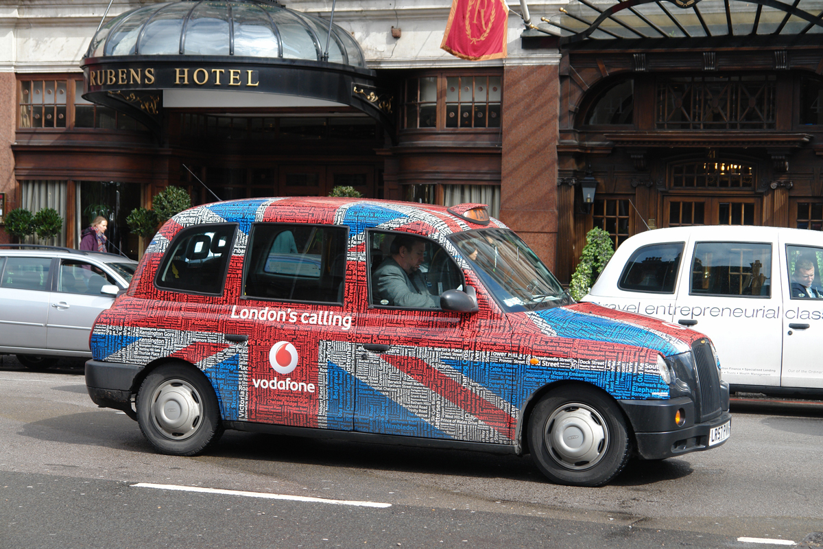 A London cab wrapped in union flag theme waiting outside a hotel for customers