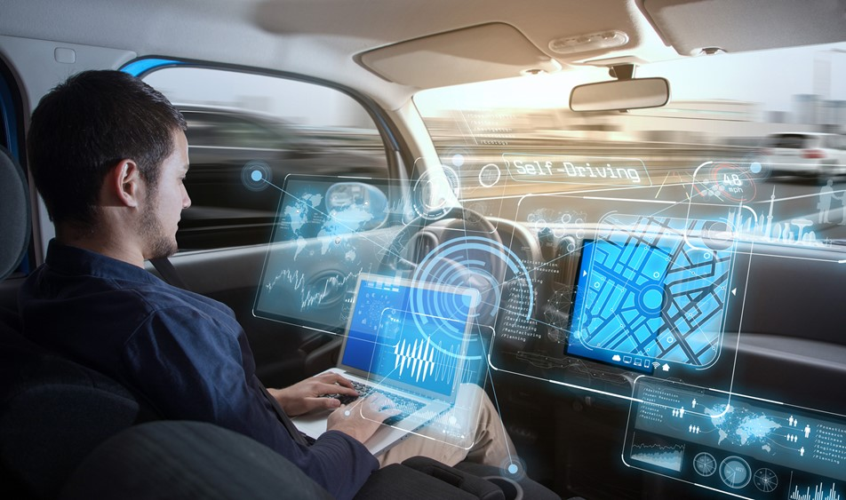 An autonomous car concept with driver on laptop while car drives itself and hologram dashboard