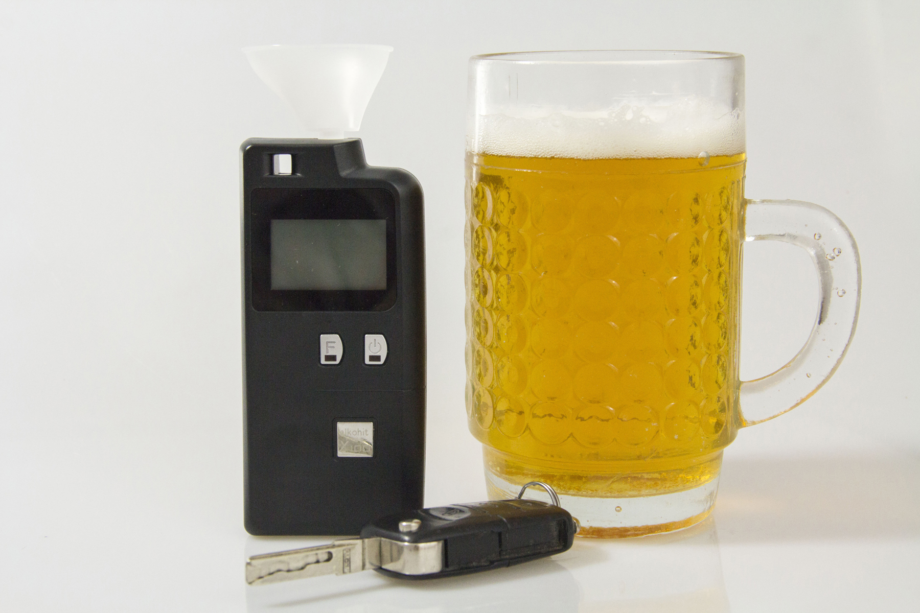 A breathalyser next to a pint of beer and car keys