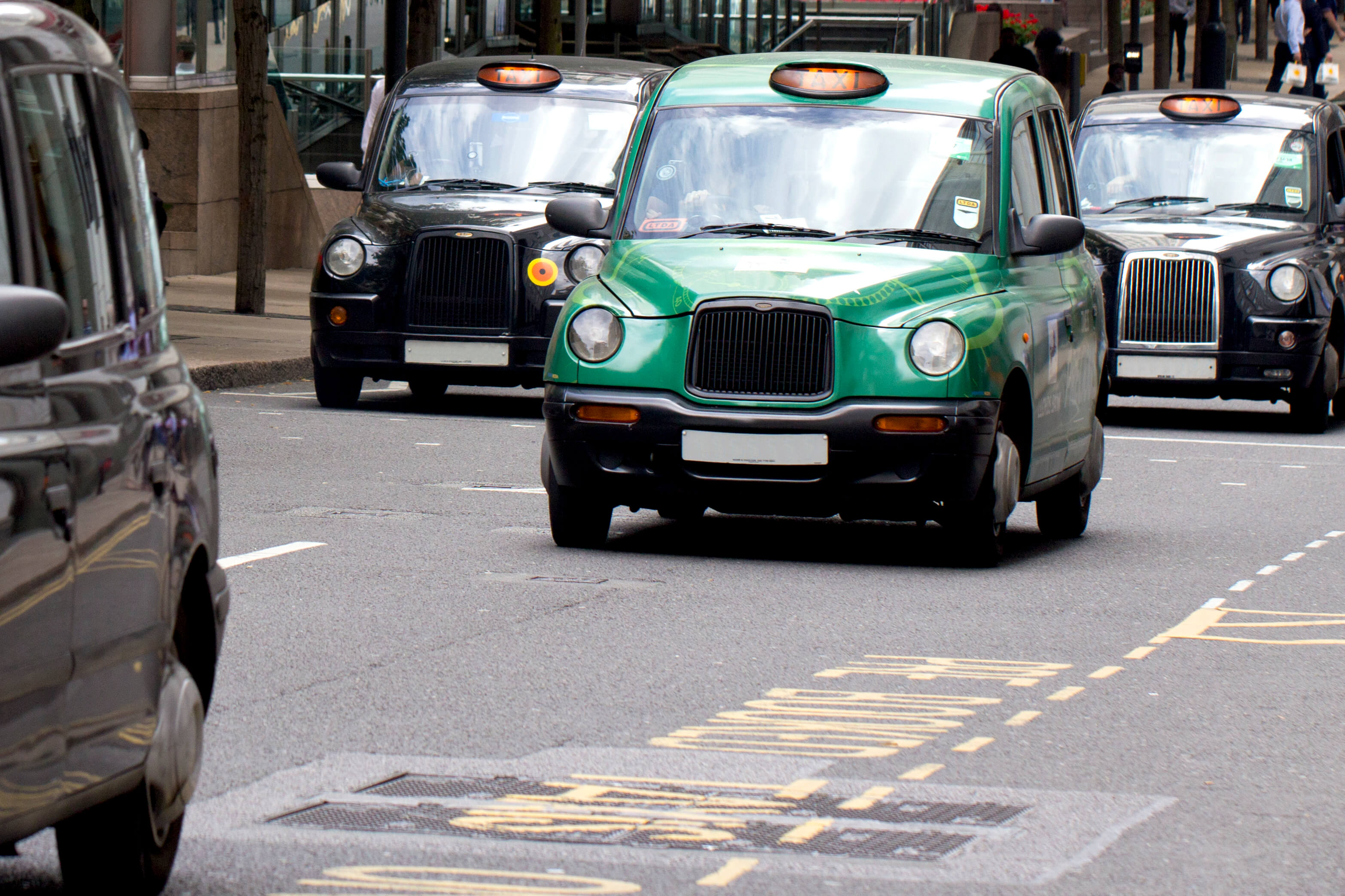 A fleet of black taxis on a London road