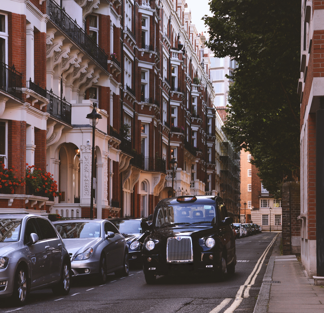A black cab driving along a residential road in London