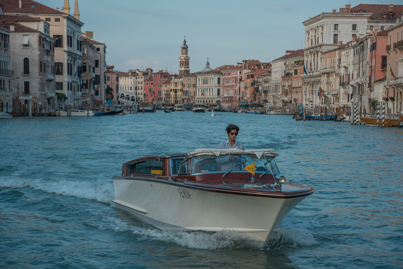 A water taxi driver across a canal in Venice