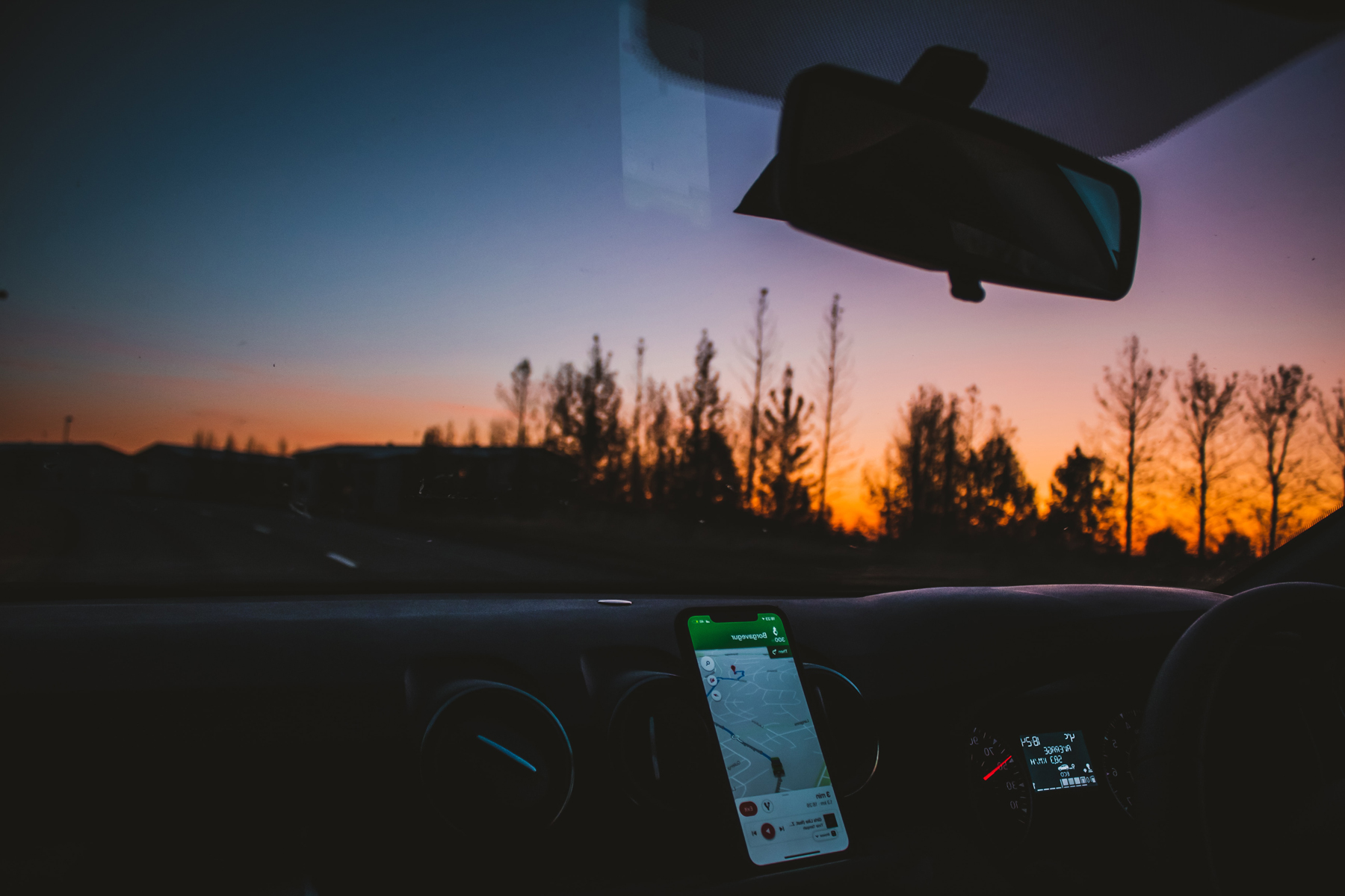 The dashboard of a minibus driving at dusk with a phone for navigation