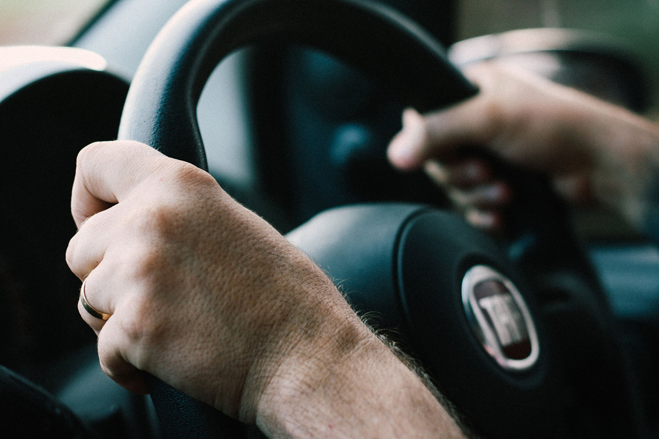 A person with both hands on the steering wheel driving